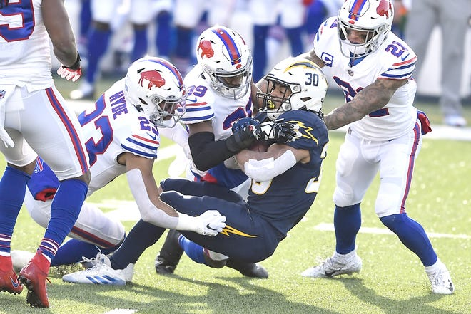 Los Angeles Chargers running back Austin Ekeler is tackled by Buffalo Bills strong safety Micah Hyde (23) and cornerback Levi Wallace (39) during the first half of Sunday's game in Orchard Park, New York.