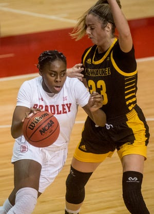Bradley's Tete Danso, left, moves the ball past Milwaukee's Megan Walstad in the first half Saturday, Nov. 28, 2020 at Renaissance Coliseum. The Braves fell to the Milwaukee Panthers 65-60.