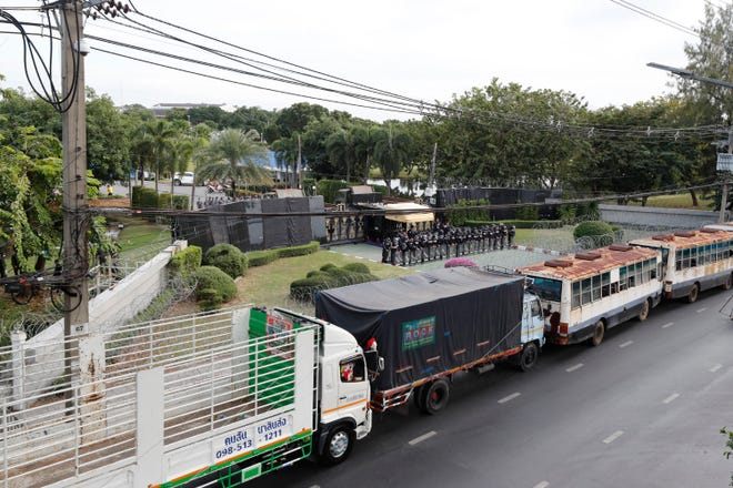 Police stand guard behind barbed wire and a row of large vehicles barricading the base entrance of the 11th Infantry Regiment, a palace security unit under direct command of the Thai king, as they await for the arrival of protesters Sunday in Bangkok, Thailand.