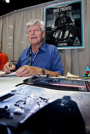 Actor David Prowse, who was the man in the black Darth Vader suit in the first Star Wars film, signs autographs at Star Wars Celebration IV in May 2007, marking the 30th anniversary of the release of the first film in the Star Wars saga, in Los Angeles, USA. The British actor, Prowse died aged 85 on Saturday, according to an announcement by his agent Sunday. (AP Photo/Reed Saxon, FILE)