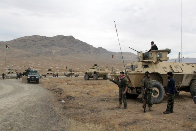Afghan national army soldiers arrive at the site of a suicide bombing in Ghazni province west of Kabul, Afghanistan, on Sunday. More than 30 people were killed on Sunday in two separate suicide bombings in Afghanistan that targeted a military base and a provincial chief, officials said. (AP Photo/Rahmatullah Nikzad)