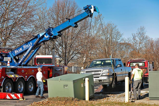 Tow truck crews and workers from Braintree Electric Light Department at the scene of a crash on Grossman Drive which knocked out power to most of the retail shops in the area on Sunday November 29, 2020 Greg Derr/ The Patriot Ledger