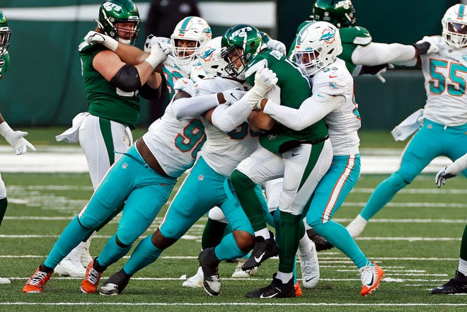 Jets quarterback Sam Darnold is sacked by Dolphins linebacker Kyle Van Noy (53) and others during a game last month.