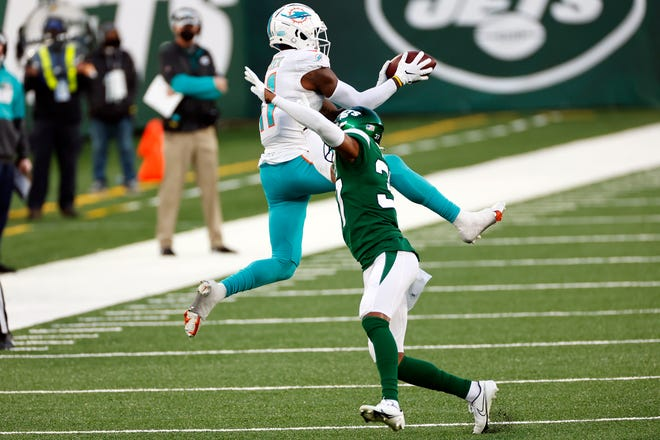 Dolphins receiver DeVante Parker makes a catch over Jets rookie cornerback Bryce Hall on Sunday.