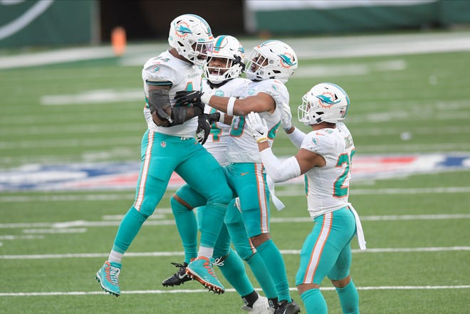 Dolphins linebacker Elandon Roberts celebrates with teammates during the victory over the Jets. Roberts had five tackles that day.