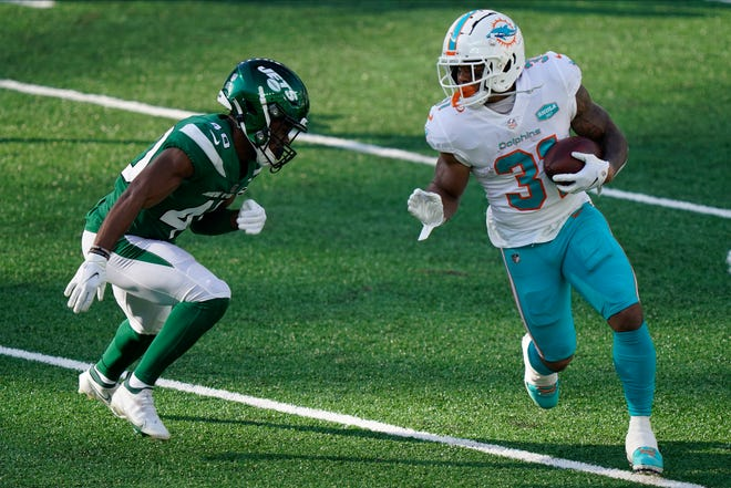 Miami Dolphins' DeAndre Washington, right, runs the ball during the first half of an NFL football game against the New York Jets, Sunday, Nov. 29, 2020, in East Rutherford, N.J.