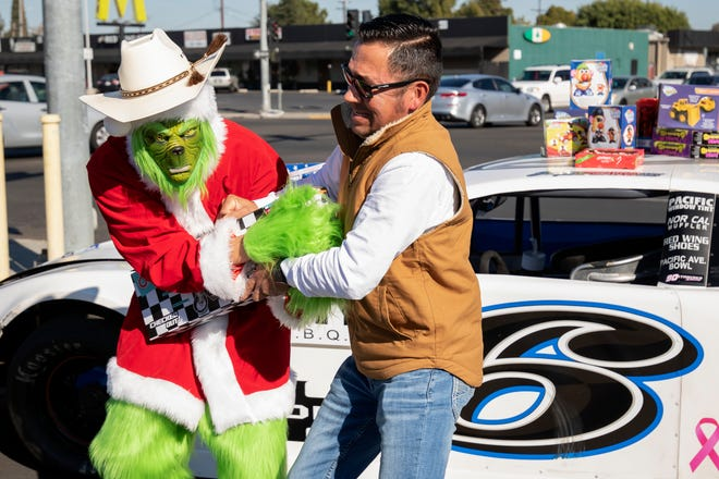 "Joey ""Joe Joe"" Stearns, 15, dressed as the Grinch, attempts to steal a gift being donated by Martin Gonzalez, Stearns' family friend, during the Stuff the Race Car toy drive at Chuck's Hamburgers in Stockton on Saturday. Toys that have been donated are set out on the cars brought in by Joey Stearns, car #6, Dominic Lopez, car #24, and Brandon Jones, car #33, during the Stuff the Race Car toy drive at Chuck's Hamburgers in Stockton, California, Saturday, Nov. 28, 2020. This is the fifth year for the Stearns organizing the toy drive and they are hoping to collect at least 1,000 toys to brighten the holidays amid a challenging year for many families."