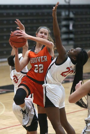 Hoover's Angela Roshak (22) splits the defense by McKinley's Nakyah Terrell (left) and Ariahna Snell (20) during their game on Saturday.
