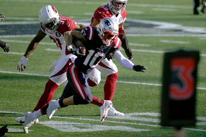 New England wide receiver Damiere Byrd, center, gains yardage past Arizona defenders Chris Banjo, left, and Jordan Hicks, rear, in the first half of Sunday's game.