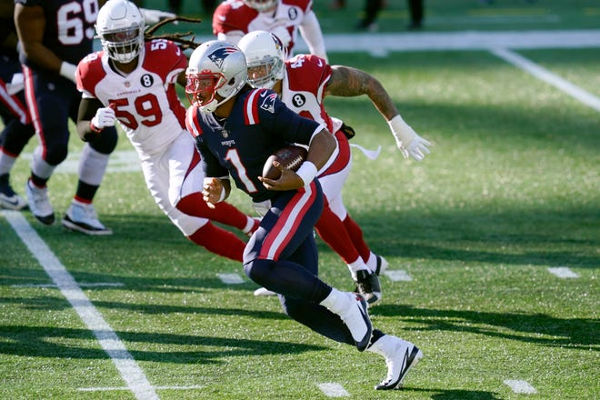 New England quarterback Cam Newton, front, scrambles away from Arizona Cardinals linebackers De'Vondre Campbell, left, and Kylie Fitts in the first half of Sunday's game.