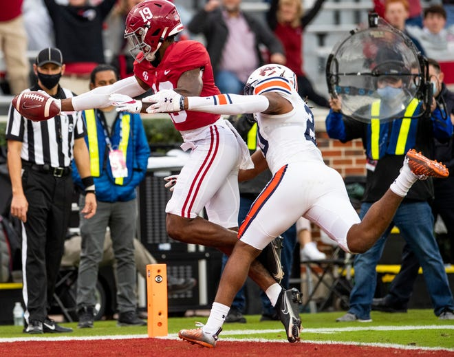 Alabama tight end Jahleel Billingsley scores a touchdown against Auburn defensive back Jamien Sherwood on Saturday during the Iron Bowl.