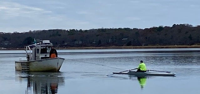 Fisherman Paul Davis gets a helping hand from rower Al Flanders Saturday. The motor on Davis' boat overheated in Town Cove and Flanders, who was passing by, towed the 7,500-pound vessel a mile to its mooring.