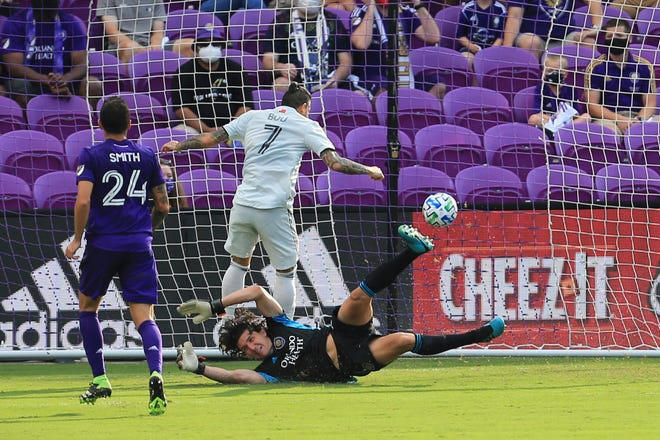 New England forward Gustavo Bou scores a goal past Orlando City goalkeeper Brian Rowe, bottom, during the first half of Sunday's game.