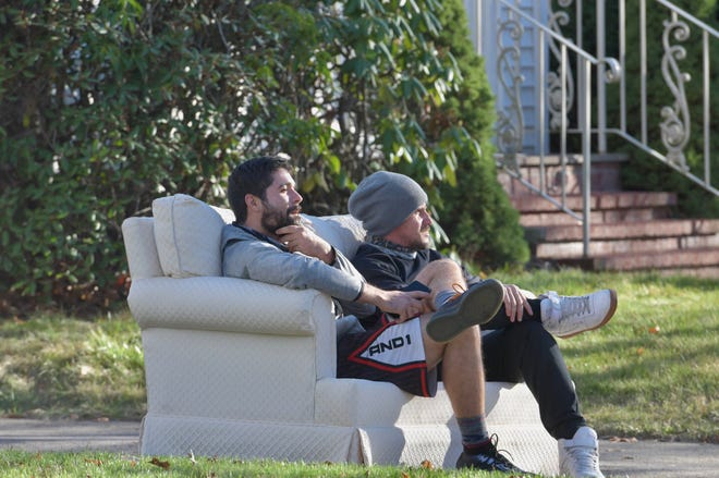 Two men take a comfy seat in the warm weather Sunday afternoon, along Russell Street facing Elm Park in Worcester.