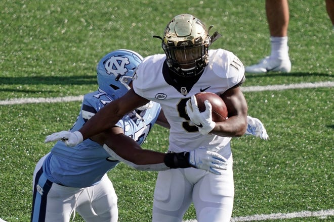 Wake Forest running back Kenneth Walker III, right, attempts to break the tackle of North Carolina linebacker Chris Collins. The Demon Deacons last played Nov. 14 against the Tar Heels as coronavirus continues to impact the program.