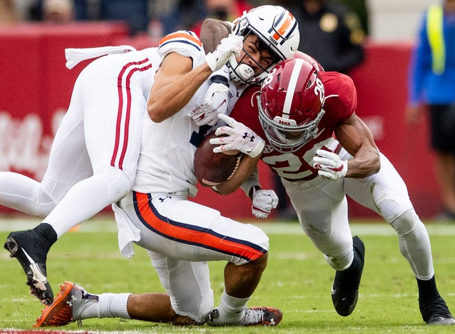 Nov 28, 2020; Tuscaloosa, Alabama, USA;  The ball comes out after Auburn wide receiver Anthony Schwartz (1) is tackled and downed by Alabama defensive back Daniel Wright and defensive back Josh Jobe (28)  at Bryant-Denny Stadium in the Iron Bowl. Mandatory Credit: Mickey Welsh/The Montgomery Advertiser via USA TODAY Sports