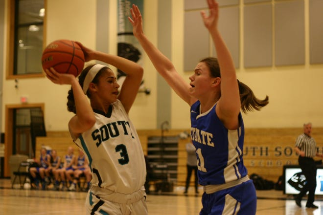 Teja Andrews holds the ball away from the Scituate defender.