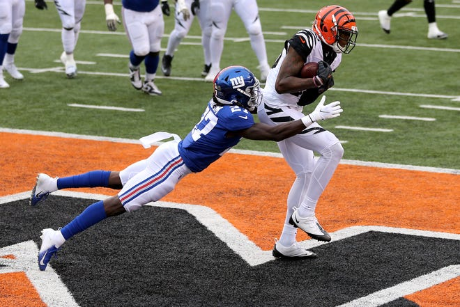 Cincinnati Bengals wide receiver Tee Higgins (85) catches a touchdown pass as New York Giants cornerback Isaac Yiadom (27) defends in the fourth quarter during an NFL Week 12 football game, Sunday, Nov. 29, 2020, at Paul Brown Stadium in Cincinnati. The New York Giants won 19-17.