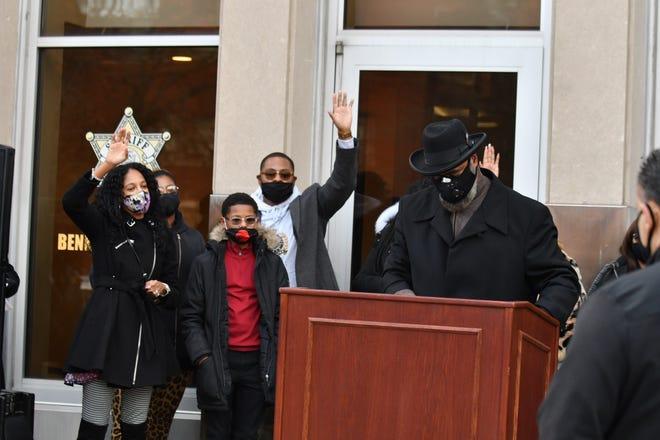 Di sebelah kiri, Tiffani Jackson, putri Benny Napoleon dan keluarganya bereaksi sementara Pendeta Alvin Jackson Sr., kanan, berdoa dalam doa berjaga untuk Sheriff Wayne County Benny Napoleon di Kantor Sheriff Wayne County pada 29 November 2020.