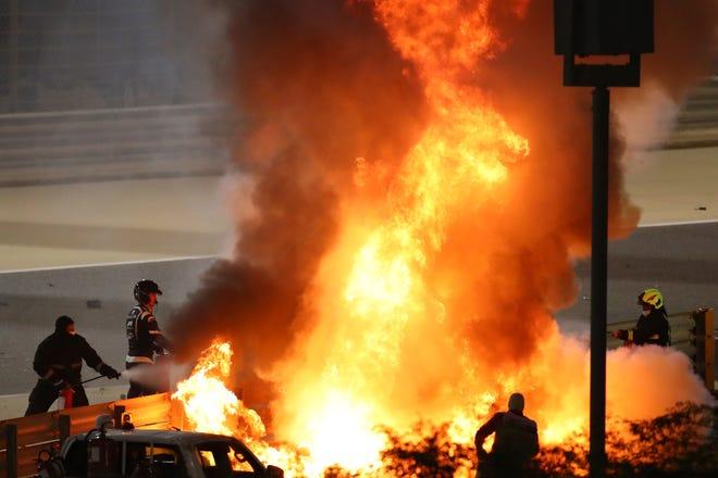 Staf memadamkan api dari mobil pembalap Haas Romain Grosjean setelah kecelakaan saat balapan Formula Satu di Bahrain pada hari Minggu.