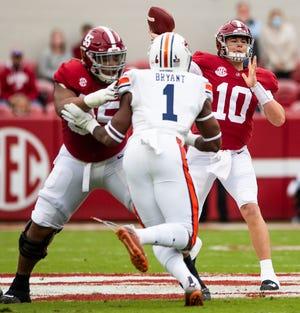 Gelandang Alabama Mac Jones melakukan lemparan ke arah pertahanan Auburn.