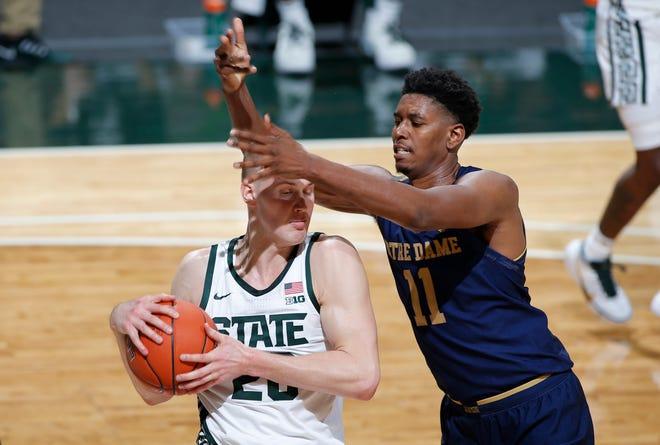 Joey Hauser dari Michigan State, kiri, dan Juwan Durham dari Notre Dame bersaing untuk mendapatkan rebound pada babak pertama.