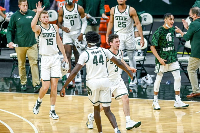 From left, Michigan State's Thomas Kithier, Gabe Brown and Foster Loyer celebrate during a timeout during the first half against Notre Dame on Saturday, Nov. 28, 2020, at the Breslin Center in East Lansing.