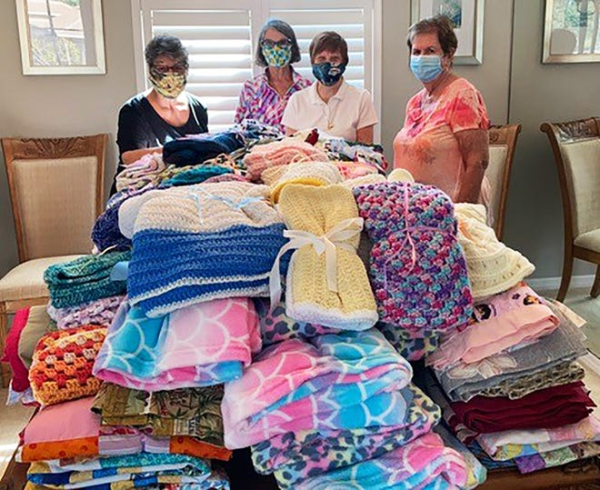 Marco Island Woman's Club Stitch Makers Aren Alter, Roz Sorber, Catherine Thomas and Donna O'Shea folded and tied bows on the 121 blankets made by club members over the summer.