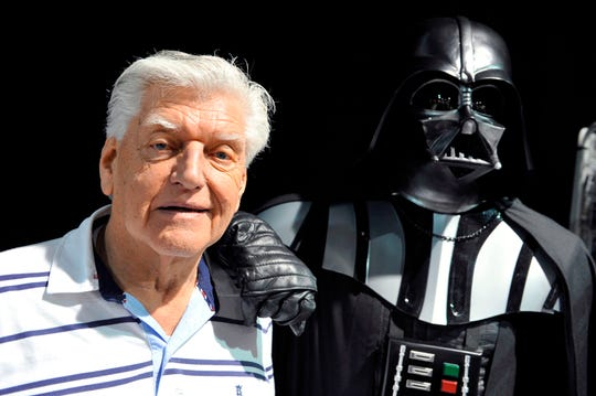 """David Prowse, seen here in 2013 with a costumed Darth Vader at a """"Star Wars"""" convention in France, has died at age 85. The British actor was the man behind the menacing black mask of the """"Star Wars"""" villain in the original trilogy."""