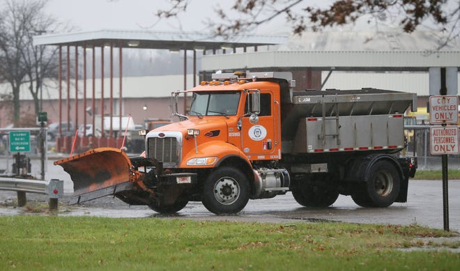 A city of Akron truck with a plow heads to a parking lot at the Bureau of Public Works Garage on Triplett Avenue in Akron Monday, Nov. 30, 2020.  [Mike Cardew/Beacon Journal]