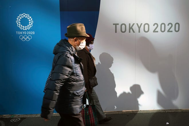 A man and woman wearing protective masks walk in front of logos of the Olympics on Monday in Tokyo. The Olympics are to open on July 23, 2021, followed by the Paralympics on Aug. 24.
