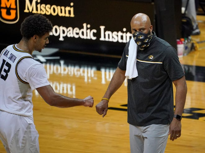 Missouri guard Mark Smith (13) bumps fists with head coach Cuonzo Martin after defeating Oral Roberts last Wednesday at Mizzou Arena.