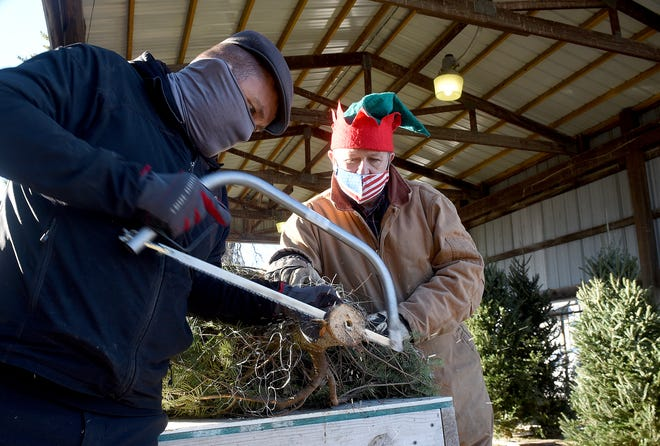 Downtown Optimist Club member Aaron Betts, left, makes a fresh cut on a Christmas tree while past president Rick McKernan holds it on Monday at the club at 1201 Grand Ave. They still have plenty left of Frazier, Balsam, Grand Fur and Scotch Pine left, ranging from $49 to $144. They are open Monday-Thursday from 1-7 p.m., Friday from 1-8 p.m., Saturday from 10 a..m.-6 p.m. and Sunday from 10 a.m.-6 p.m.