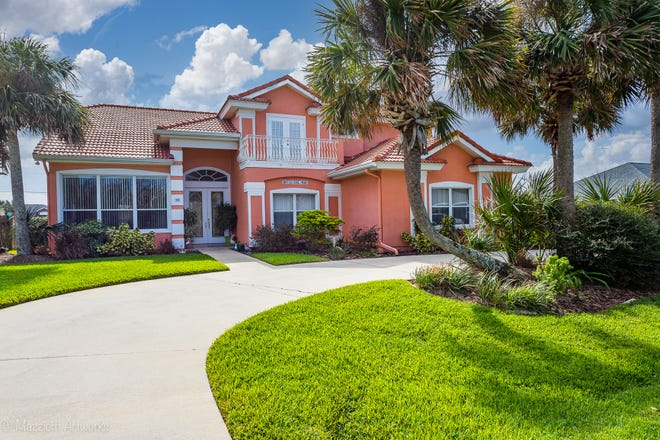 An extra-deep, circular driveway, with room to handle all your parking needs, leads up to this lovely Palm Coast pool home, which is topped with a tile roof.