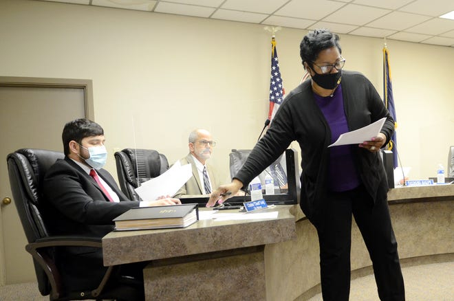 Donaldsonville Finance Director Sandra Cost Williams hands reports to City Attorney Spencer Long and council members during the Nov. 24 meeting.