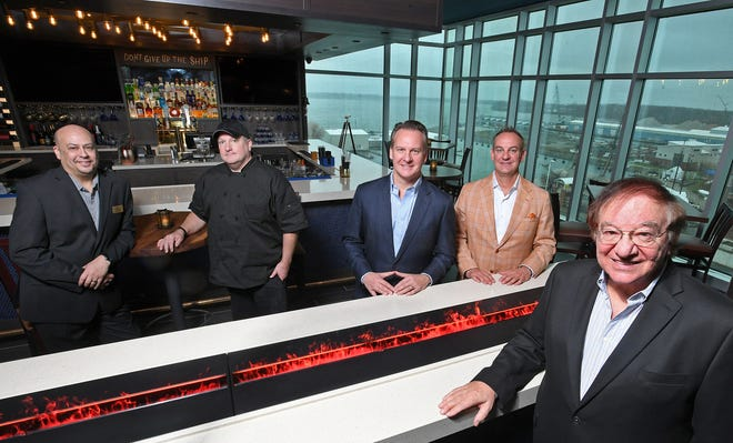 Shown, Nov. 30, 2020, near an LED fireplace (foreground) and the restaurant's bar, background, at Oliver's Rooftop are, from left: General Manager Jim Markham, Chef Rick Pohlman, Scott Enterprises vice presidents and part owners Nick Scott, Jr., Chris Scott and president Nick Scott, Sr. Oliver's is a new restaurant located on the eighth floor of the 94-room Hampton Inn & Suites, owned and operated by Scott Enterprises on Erie's bayfront. The hotel has been open since August. The restaurant is scheduled to open on Dec. 1, 2020.