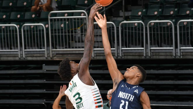 Jonathan Aybar of North Florida (32) jumps center against Miami's Nysier Brooks during Sunday's game in Coral Gables.