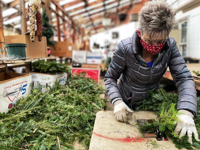 Owner Marjorie McVey assembles wreaths at The Greenhouse, 963 E. Main St. on Nov. 30, 2020.