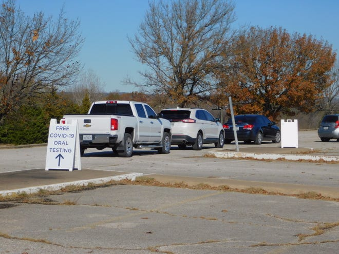 Vehicles line up for free COVID-19 tests in the parking lot of Midway Mall Monday morning.
