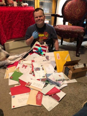Danny Moreland, 34, of Peoria, prepares to look through a heap of cards, letters and packages that came through the mail from across the globe.