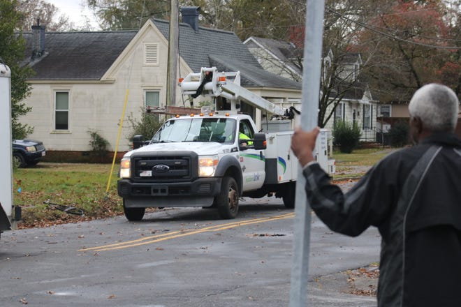 A man watches crews work on North Herritage Street near Highland Avenue Monday, Nov. 30, to restore power to residents who lost internet, cable, and phone services after an SUV knocked down utility poles on Sunday night.