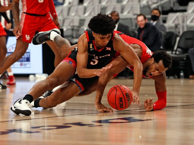 Texas Tech's Micah Peavy, left, and Justin Gorham scramble for a loose ball during the Red Raiders' 64-53 loss Sunday at Dickies Arena in Fort Worth.