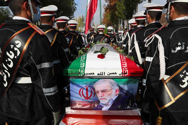 Military personnel stand near the flag-draped coffin of Mohsen Fakhrizadeh, a scientist who was killed on Friday, during a funeral ceremony in Tehran, Iran, on Monday.