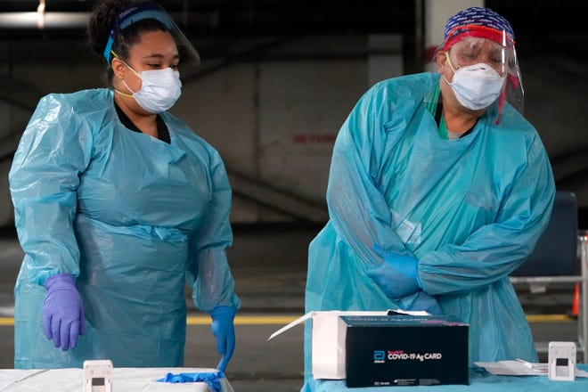 Nurses check on the status of rapid COVID-19 tests at a drive-through testing site in a parking garage in West Nyack, N.Y., on Monday. The site was only open to students and staff of Rockland County schools in an effort to test enough people to keep the schools open for in-person learning.