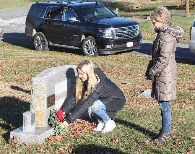 Mary McKeown stands and watches her niece, Lauren Kelly of Atlanta, Ga., place a decorative wreath Saturday morning at the Oakland Cemetery grave site of McKeown's father, U.S. Navy veteran Hugh M. Kelly, as they participate in the Moberly Altrusa Club's Wreaths of Honor event held Nov. 28.