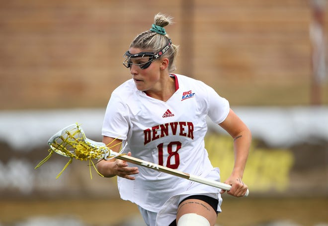 Published Caption:  The University of Denver's Molly Little, a Tiverton resident, cradles the ball and looks up the field before making her next move. [CLARSKON CREATIVE PHOTOGRAPHY / JAMIE SCHWABEROW]