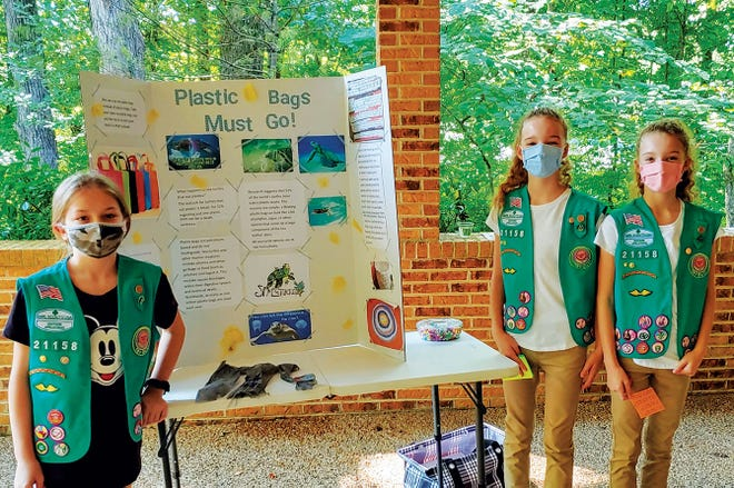 Junior Girl Scouts Stephanie Kenworth, from left, Lily and Lindsay Faulkner present their Bronze Award project, 'Plastic Bags Must Go.'
