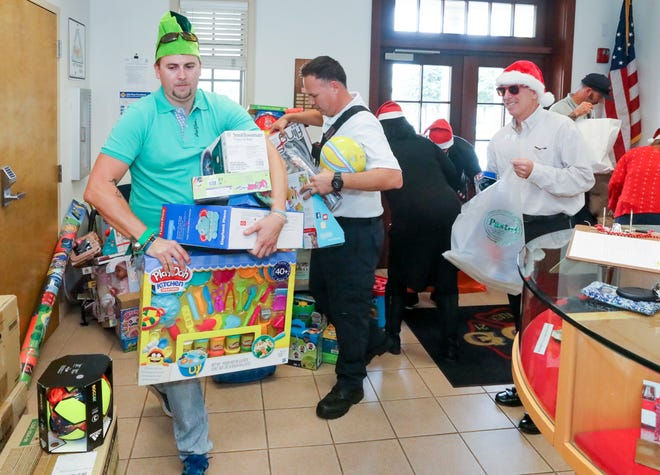 Woody McQuade of YMCA of the Palm Beaches works with YMCA staff members and Palm Beach firefighters to pick up toys from the Holiday Toy Drive at Central Fire Station in 2019.