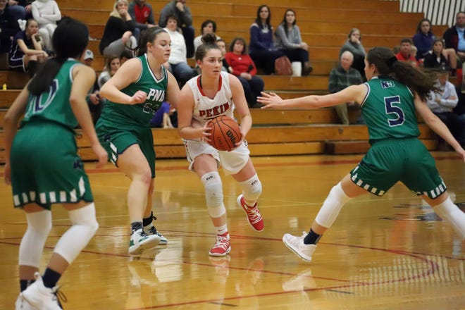 Pekin's Taylor Goss passes to a teammate while being watched by three Peoria Notre Dame players during a game last season.