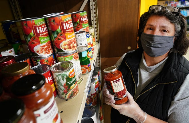 Tammy Joslyn, executive director of Operation Blessing in Portsmouth, looks over the food supply Monday morning after the shelves were just stocked.